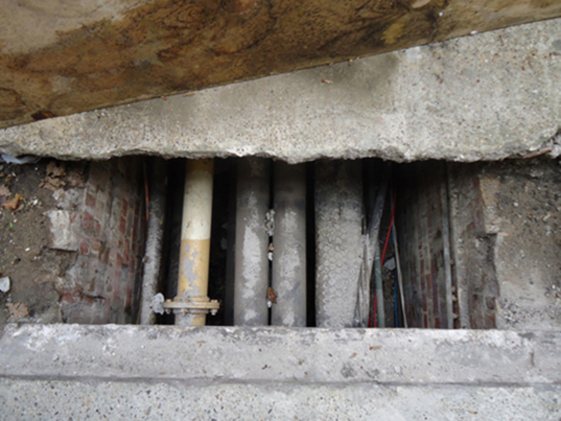Removed crumbling concrete cover showing heating pipes underneath