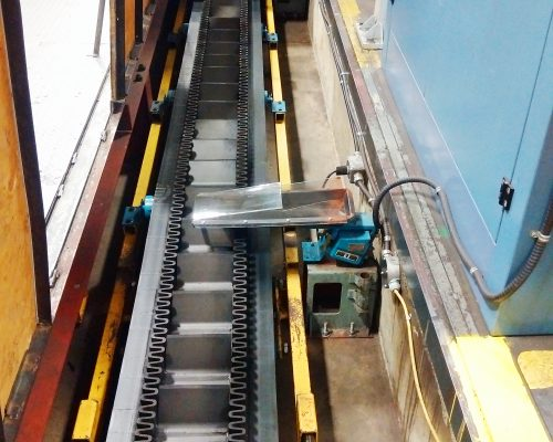 Underfloor conveyor in trench takes products from presses to packaging