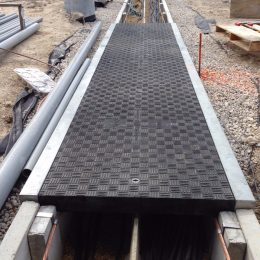 Trenwa's heavy-duty precast concrete road crossing trenches topped with Fibrelite's traffic rated composite trench covers